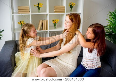 Mom with two daughters playing in the tickle