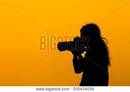Silhouette of a girl photographer with DSLR camera and tele lens at sunset on rooftop. Photographer life concept.