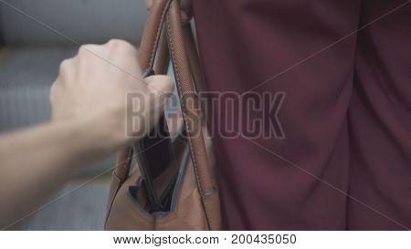 Pickpocket Thief Is Stealing Smartphone From Orange Handbag.