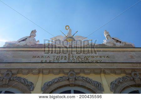 VIENNA, AUSTRIA - APR 30th, 2017: Statue of guardians at Gloriette in Schonbrunn palace in Vienna, Austria. Built in 1775 designed by architect Johann Ferdinand Hetzendorf von Hohenberg, clear sky with the sun in the background.