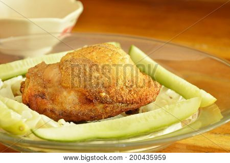 fried chicken thigh dressing salt and pepper with vegetable on plate