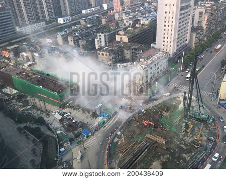 WUHAN, CHINA - AUGUST 16 2017: dust cloud spreading in city street after a building collapse during demolition