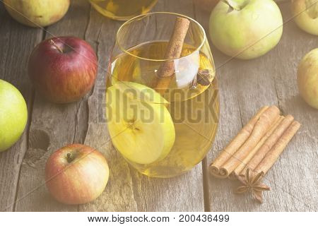 Apple Juice In Glass With Cinnamon And Anisetree On A Dark Wooden Background. Toning