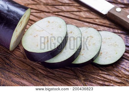 Eggplant and eggplant slices on wooden cutting board horizontal closeup