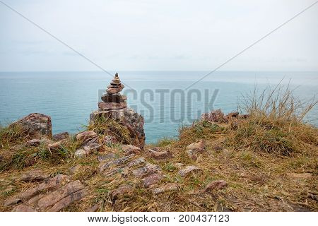 Balance stone stack on cliffside with seascape background at Khao Laem Ya Mu Ko Samet National Park in the Gulf of Thailand.