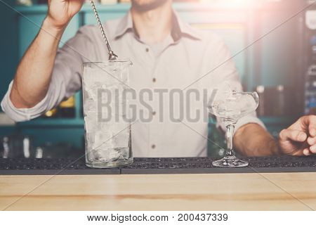 Professional bartender in bar mixing ice in glass for drink closeup