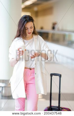 Young woman in international airport walking with her luggage.