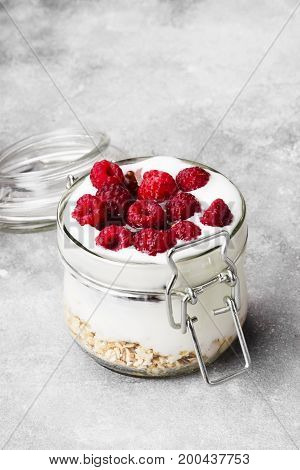 Glanola In Glass Jar With Raspberry And Mint On A Gray Background
