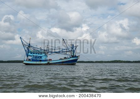 The fishing boat in the sea is slowly moving before reaching the catch