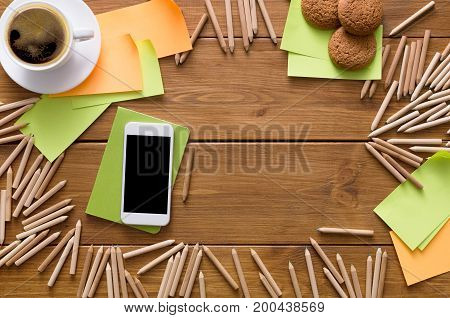 Buying stationery online. Top view on artist workplace with credit card, lots of pencils, mobile, sticky memo notes and cup of morning coffee with cookies on wooden desk background with copy space