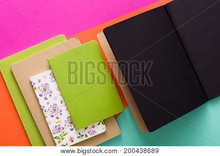 Stylish mockup with set of various colorful notebooks and black open sketchbook on creative multicolored work space background, copy space, flat lay, concept of start-up and stationery supplies