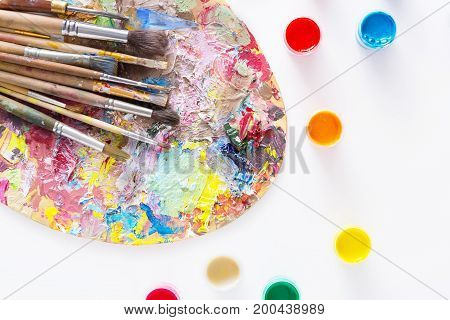 Artist's palette with colorful paint strokes, gouache jars and paintbrushes on white isolated background, top view, flat lay, object
