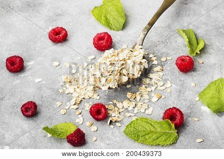 Glanola In Spoon With Raspberry And Mint On A Gray Background