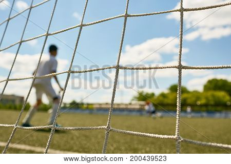 Back view portrait of teenage goalkeeper standing in gate during match between junior football teams, shot from behind gate net