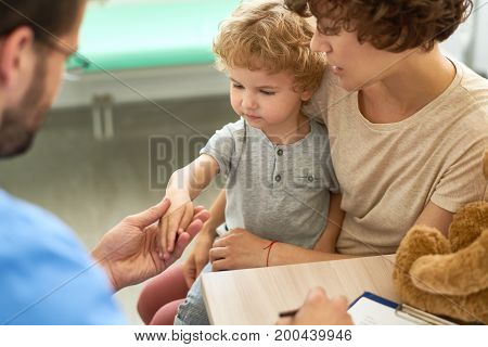 Closeup portrait of cute curly boy sitting on mothers lap during medical checkup, doctor inspecting child during appointment in office