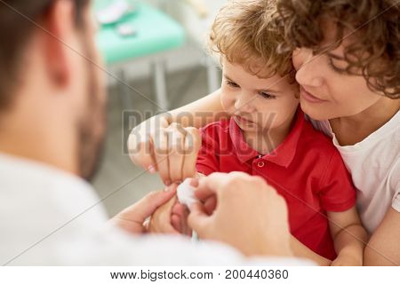 Portrait of adorable little boy with mother visiting doctor to bandage hurt finger