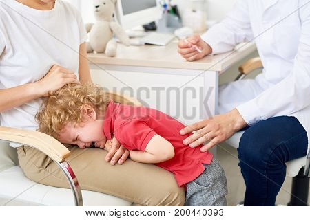 Portrait of little boy throwing hysterical tantrum at doctors office  refusing to be vaccinated
