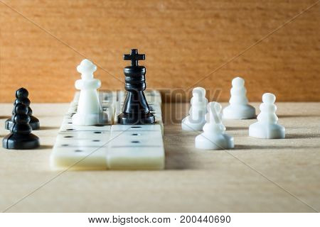 Composition of chess pieces and dominoes on a wooden background