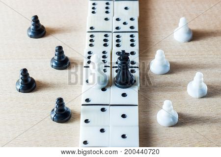 The chess king and queen stand on a path lined with dominoes surrounded by their servants pawns on a wooden background