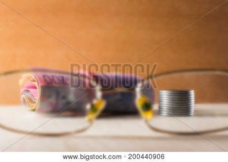 Accounting paper notes and metal coins view through the transparent glasses of eye glasses on a wooden background
