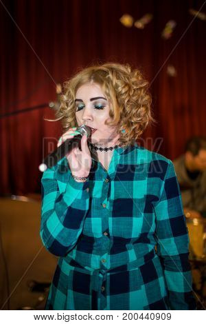 Singing girl with a microphone at a concert