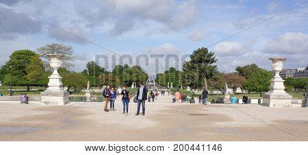 ParisFrance- April 30 2017: The garden of the Tuileries. Along the avenue Santral go people