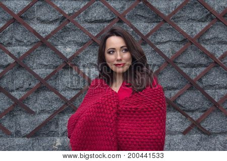 Beautiful thoughtful woman with a red shawl. People