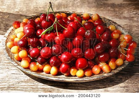 Plate with fresh ripe cherries on wooden table