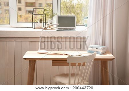 Modern comfortable workplace with laptop near window sill at home