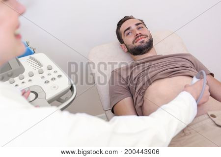 Young man undergoing ultrasound scan in clinic