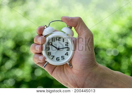 hand holding a white alarm clock as business or time countdown concept with green bokeh in summer sun shine.