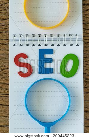 SEO Search engine optimisation concept as colorful alphabet abbreviation SEO with magnifying glass and note paper on the wooden table.