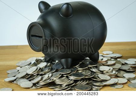 black piggy bank on top of coins as saving or financial wealth concept.