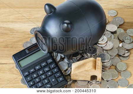 black piggy bank with calculator and coins as saving or financial wealth concept.