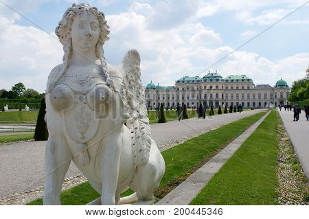 VIENNA, AUSTRIA - APR 30th, 2017: Upper Belvedere Palace with a close-up of a statue of a horse at the entrance on a sunny day with blue sky and clouds in summer and tourists walking.