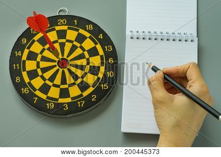 hand holding pencil on white note paper with dartboard as Goals or Target concept.