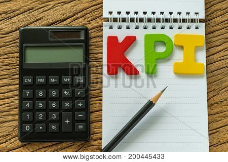 white paper note and colorful wooden alphabet KPI with calculator.