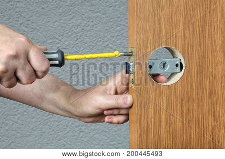 Screwdriver in the hands of a locksmith close-up replacement of the lock in the interior door.