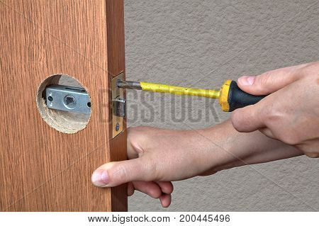 Installing the door handle with a latch in the interior doors close-up hands of the installer with a screwdriver.
