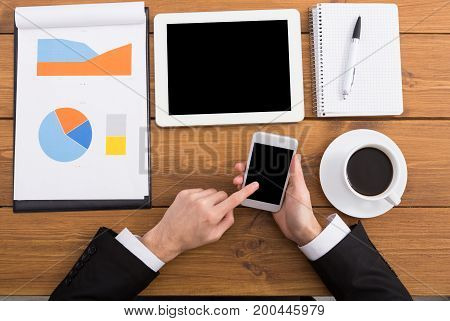 Businessman using phone at workplace. Man working with portable computer, copy space on display, top view, close up