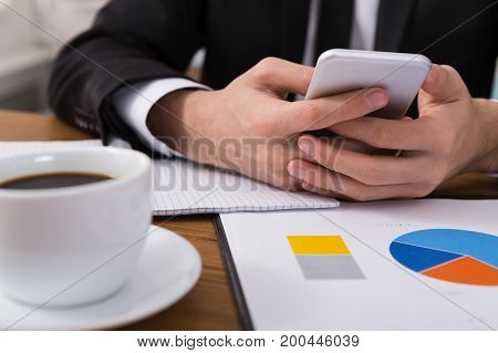 Male using phone at workplace. Freelancer working with portable computer, side view, close up