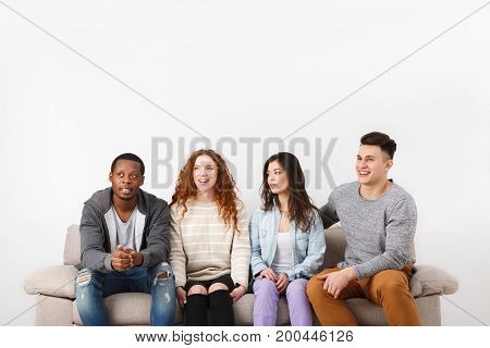 Happy multiethnic friends, casual people having fun, sitting on couch indoors and laughing