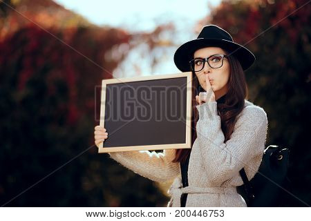 Student with Blackboard Holding a Secret Making Quiet Sign