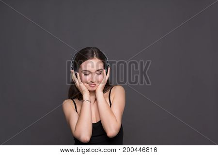 Woman enjoying music in headphones with closed eyes, standing on gray studio background