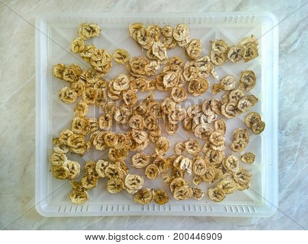 Dried bananas - chips on a light plastic tray on the kitchen table