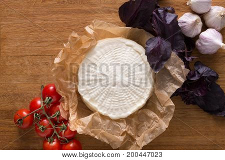 Cheese platter, homemade indian paneer cheese on wooden board with herbs, top view