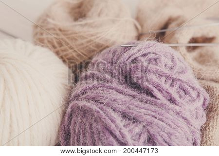 Needlework and handicraft concept. Colorful soft balls of yarn with handmade cloth, instruments for knitting.
