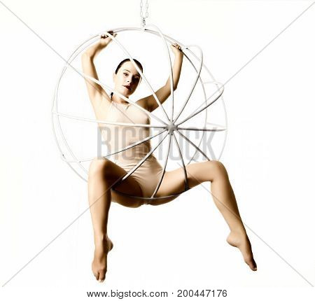 sexy woman in a beige swimsuit on a metal swing on a white background.