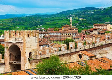 View of the small medieval Italian town of Soave, situated close to Verona. Colored houses, brick wall with watch tower and green hills on the background. Province of Veneto, Italy
