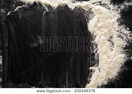 Flour on black, baking background with copy space